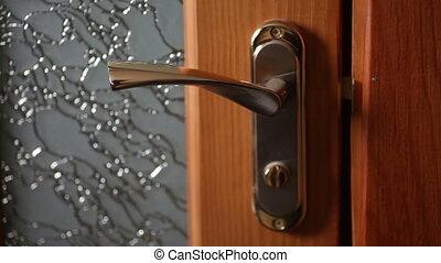 Woman hand opening wooden door. Holding a gold door handle.
