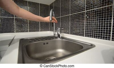 Woman hand opens a water tap in  kitchen.