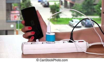 woman hand plug charger cable in extension socket and hold...