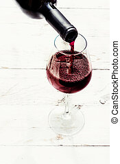 Woman hand Pouring red wine from bottle into the wine glass on white wooden background with copyspace