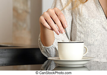 Woman hand preparing a cup of coffee