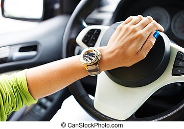 Woman hand pressing on a car horn