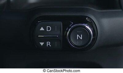 Woman hand pushing reverse gear button in car
