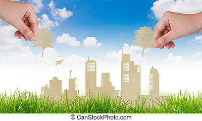 Woman hand put Paper cut of tree over city and grass with...