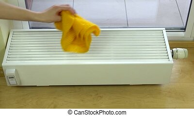 woman hand put yellow scarf and red gloves on radiator at...