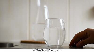 Person hand puts a handful of pills on the table. A glass of clean water and activated carbon against gastrointestinal diseases.