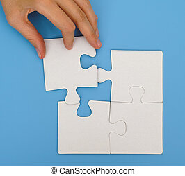 Woman hand putting final piece of puzzle