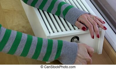 woman hand red nail reduce warm by radiator thermostat room. 4K