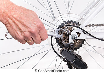 Woman hand repair bicycle whee with screw key - studio shoot...