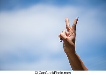 Woman hand showing two fingers as victory sign on blue sky with white cloud background