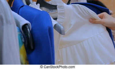 Woman hand sorts out hanger with clothes - Close up shot -...