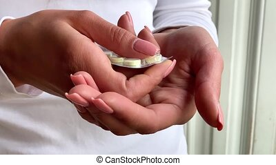 Woman hand take pills from blister pack. Close up of female...
