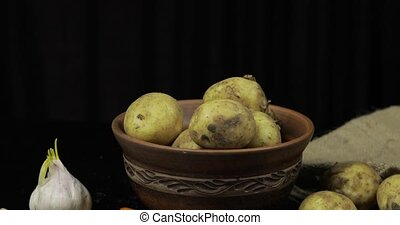Woman hand takes potatoes in pile one by one. Dirty raw potatoes on a plate