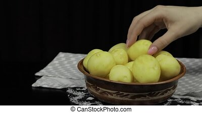 Woman hand takes potatoes one by one. Washed fresh raw potatoes