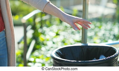 Close up portrait of a woman hand throwing trash into bin in a park in slow motion