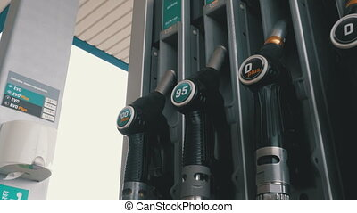 Woman hand using fuel nozzles at a gas station. Filling...