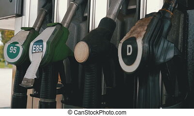 Woman hand using fuel nozzles at a old gas station. Filling...
