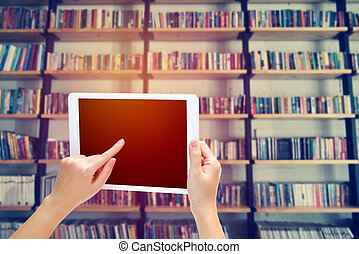 woman hand using the phone tablet with book shelf background