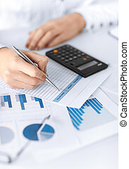 woman hand with calculator and papers - picture of woman...