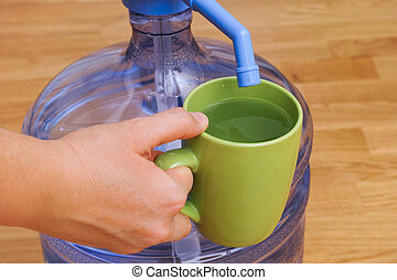 Woman hand with cup full of water near bottle with water pump.