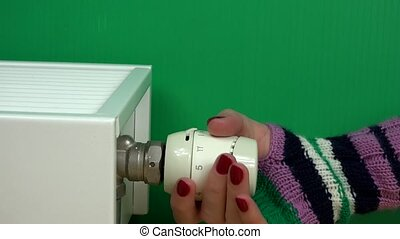 Woman Hand with glove Adjusting Temperature Of Radiator Thermostat on green.