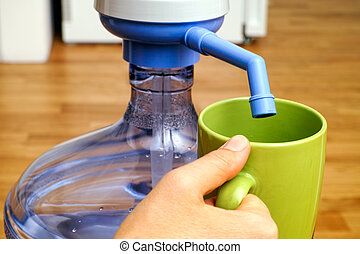 Woman hand with green cup near bottle with water pump.
