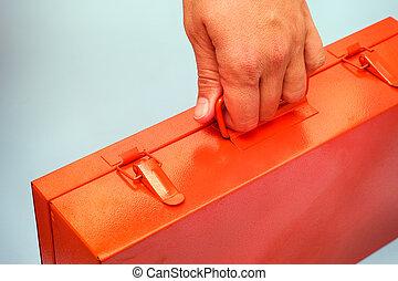 Woman hand with orange metal box.