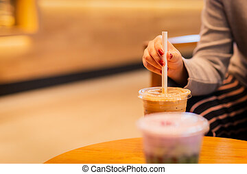 Woman hand with paper straw in plastic glass of cold coffee.