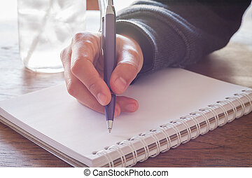 Woman hand with pen writing on notebook