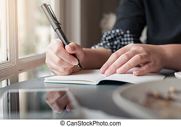 Woman hand with pen writing on notepad