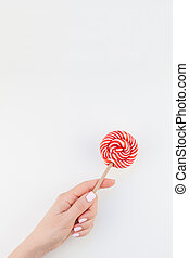 Woman hand with red lollipop