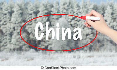 Woman Hand Writing China with a marker over winter forest.
