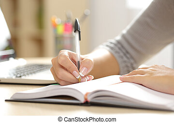 Woman hand writing in an agenda at home