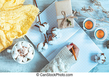 Woman hand writing in notepad, cup of coffee, dried rose and autumn leaf