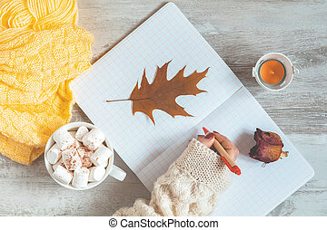 Woman hand writing in notepad, cup of coffee, dried rose, candle and autumn leaf