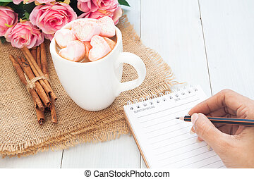 Woman hand writing on notebook with beautiful hot drink on table
