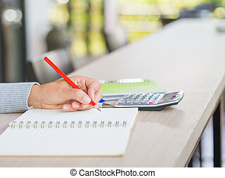 Woman hand writing with red pencil and calculator on working table. Business and education concept.