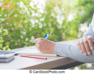 Woman hand writing with white pen, red pencil and calculator on working table and tree leaves background. Business and education concept.