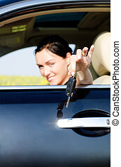 Woman handing a set of keys out of a car