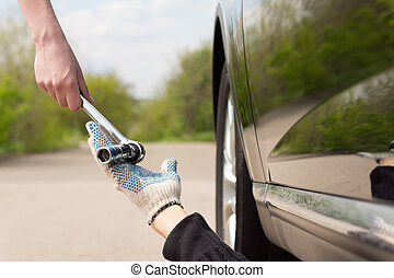 Woman handing a socket wrench to a mechanic