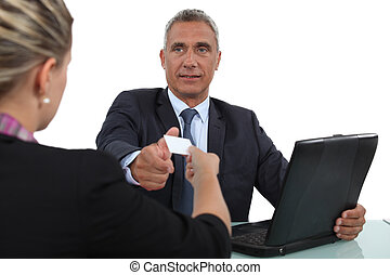 Woman handing over her business card during a meeting
