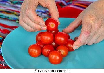 Woman hands arrange Cherry tomatoes in a plat