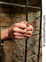 Woman hands behind the bars