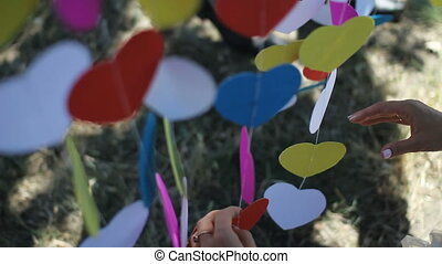 Woman hands correct colored hearts on a string sway in the wind. Original wedding arch