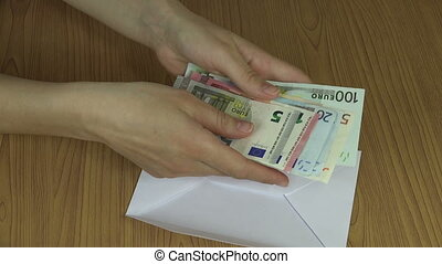Woman hands count money euro banknotes and put in envelope....
