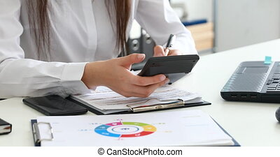 woman hands counting on calculator and filling documents in modern office.