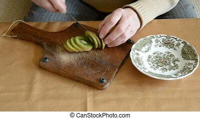 woman hands cutting kiwi fruit