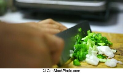 Woman hands cutting vegetables on wooden board.