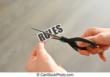 """Woman hands cutting with scissors a printout reading """"RULES"""""""
