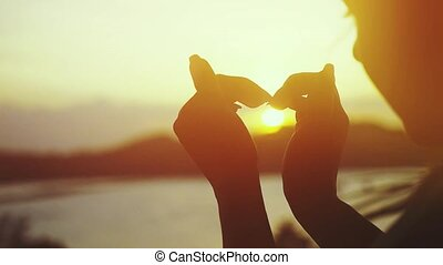 Woman hands forming a heart at amazing sunset over the sea on tropical island. slow motion.